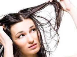 Mulher olhando com um olhar preocupada para o seu cabelo oleoso